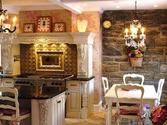 Kitchen Design Inspirations: The exposed stone wall in this old-fashioned dining area serves as a soft backdrop for the pink hues throughout the room. The small, white dining table complements the nearby kitchen cabinets, and the chairs echo the soft curves of the cabinet and mantel molding. Design by Dave Stimmel. From DIYnetwork.com