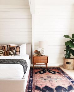 Modern bedroom design with global style featuring white shiplap walls, a beige upholstered platform bed, white bedding and ethnic patterned textile pillows and throw blanket, a mid-century modern wood bedside table, vintage area rug, and a fig tree in a woven basket - Global Decor-& Bohemian Decorating Ideas
