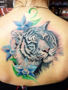 Blue Flowers And White Tiger Head Tattoo On Upper Back