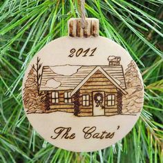 """Wood Burned Log Cabin Personalized Ornament- The ornament measures 4"""" wide x 4 1/2"""" tall x 1/8"""" thick and has been protected with a high quality varnish."""