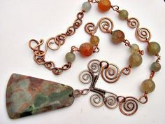 A beautiful Agate pendant with translucent colors of white, rust and greens dangles from a hanger of spiraled, woven, copper wires.  Large agate beads in soft shades of greens,  blues and pale orange