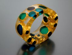 Bangle by Karen McCreary. . Transparent acrylic, hand-carved and layered with colored lacquer, 22 karat gold leaf;  fabricated silver elements.