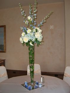 tall table arrangement. wedding flowers. event flowers. party flowers. white roses, blue delphinium, blue hydrangea, white miniature calla lilies. italian ruscus in vase. http://thebloomingidea.blogspot.com