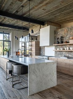 a contemporary chalet kitchen with a stone wall, a reclaimed wood ceiling, stone countertops and a modern black chandelier - DigsDigs Kitchen Styling, Rustic House, Rustic Kitchen Design, Rustic Kitchen, Modern Black Chandeliers, Modern Kitchen, Rustic Modern Kitchen, Kitchen Design, Rustic Kitchen Tables