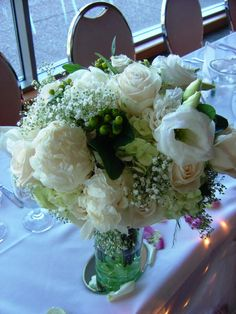 White Peony Bridal Bouquet. This beautiful bouquet contains white peonies, green hydrangeas, cream roses, white double lisianthius, green hypercium berries, and baby's breath.