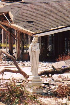 The Blessed Mother statue (which had no protection) at Our Lady of the Gulf Catholic Church in Bay St. Louis, MS after Hurricane Katrina -- Note the rectory behind it in ruins.