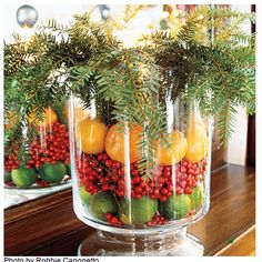 Create an Arrangement with Fruit and Greenery  Use a glass hurricane or vase to create an arrangement that will last throughout the Christmas season by filling the jar with a layer of limes, red holly berries, and lemons. Top it off with stems of greenery.