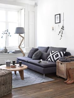 An example of a dark couch with a light wall and wood.