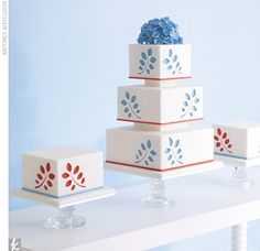 Cake Trios Small white square cakes mimic the main attraction -- a white-three-tiered fondant cake with a punched-out blue and orange vine pattern. Blue sugar-made hydrangeas soften the look while simple risers (no plastic columns here!) add height to the display.
