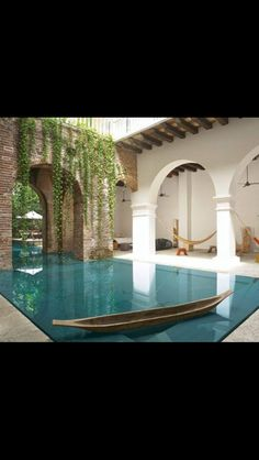 Shallow reflecting pool designed by architect Alberto Burckhardt, with border of mirrorlike gray stone, flows into deeper swimming pool beyond brick arches. Trough along pool's edge recirculates water and makes surface appear flush with patio.