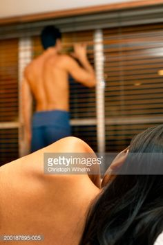 Woman watching man looking out of window