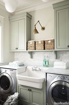 Beautiful colour in this laundry, with open shelving and baskets for added storage