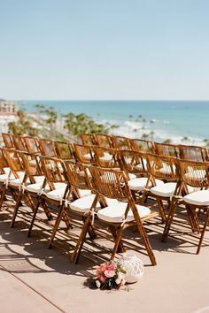 Seaside wedding ceremony, beachy chairs with white cushions, pink floral arrangements lining the aisle // Anna Delores Photography