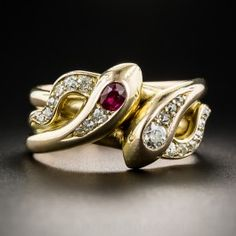 A diamond-headed serpent snuggles cheek-to-cheek with its ruby-headed lover and coils thrice around your finger in this superb double snake ring, dating from the-turn-of-the-last-century. Artfully handcrafted in richly gleaming 14K rosy yellow gold. Currently ring size 8.