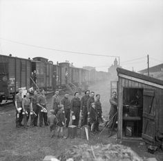 Men of 607th Railway Construction Company, Royal Engineers, queuing for rations in the railyard at Weert, The Netherlands, 1 December 1944.