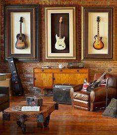 Nesta sala de música de estilo clássico, instrumentos emoldurados foram pendurados na parede e complementam a decoração composta por parede de tijolos, revestimentos em madeira e poltrona de couro.