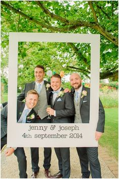 Groomsmen portrait with pastel pom poms hanging from the trees & personalised frame prop - Image by Kerrie Mitchell - Pastel Wedding With Shabby Chic Styling At Gaynes Park With Bride In Lace Fishtail Sarah Janks Gown With Groom In Powder Blue Bowtie From Mrs Bowtie And Images By Kerrie Mitchell