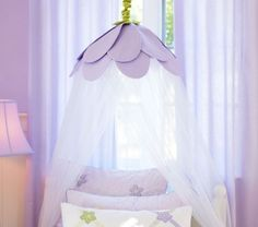 Love this Lavender Petal Canopy! You could easily create a similar look by hanging a lamp shade from the ceiling and gluing on some netting. What a nice addition to a little girls room!
