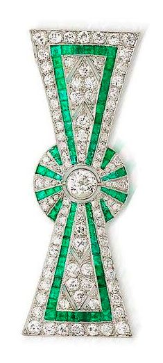 An art deco diamond and emerald bow brooch, circa 1925 The stylised ribbon bow with pierced and millegrain detail, set throughout with rows of old brilliant-cut diamonds and french-cut emeralds, a larger collet-set old brilliant-cut diamond at the centre, diamonds approximately 3.25 carats total, partial French maker's mark, partial French assay mark.