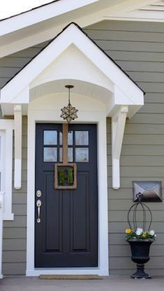 Quick add on over front door. exterior paint color Crownsville Gray by Benjamin Moore - Nice door overhang! These colors match our house. We used Storm Cloud Gray and Baby Seal Black for the door with white trim. Love this color combination. Exterior Paint Colors For House, Paint Colors For Home, Paint Colours, Gray Exterior Houses, Exterior Paint Combinations, Cottage Exterior, Blue House Exteriors, Exterior Paint Ideas, Green House Siding