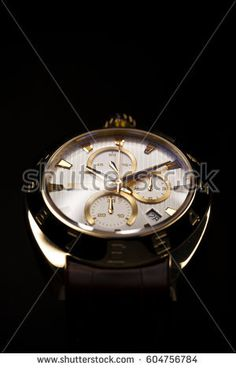 A Swiss men's mechanical wrist watch with golden finish, brown leather wristband, tachometer and a chronograph. Isolated on black background.