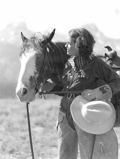 """""""Why Don't You Comb Your Hair?"""" A cowgirl and her horse in front of the Tetons in Northwestern Wyoming by Harrison R. Crandall, 1930s-1940s This was a typical photo used to promote the """"dude"""" ranches. City folks could experience """"the west"""" at these ranches through guided trail rides, camping and chuck wagon cooking. The industry thrived during the golden era of the cowboy. Wyoming State Archives."""