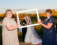 Mother and grandmother of the bride and groom hold up a picture frame for the newlyweds to pose behind.