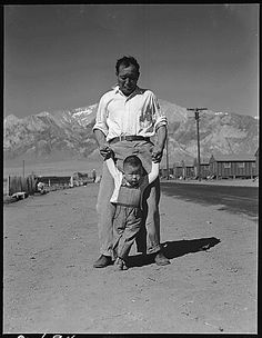 537991: Manzanar Relocation Center, Manzanar, California.  Grandfather of Japanese ancestry teaching his little grandson to walk at this War Relocation Authority center for evacuees