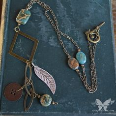 The Aqua Terra Jasper stones in lovely turquoise look beautiful with the antiqued brass findings in this boho-style necklace.  The lightweight brass diamond is adorned with a unique marquise link chain, an antiqued silver feather, a brass button and a round Jasper stone.    The peanut shaped ch...