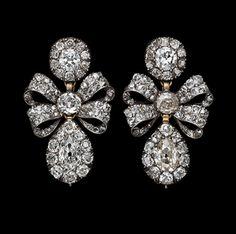 Silver earrings, the top cluster joined to the drop shaped pendant by a bowknot, ribbons meeting at a centre cluster, set throughout with diamonds. English c. 1760