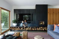 """Eames Lounge Chair and Ottoman from This Kansas City Home Looks Like… - Hufft Projects designed the blackened steel """"fireplace wall,"""" which includes a Lennox wood-burn - Tv Above Fireplace, Home Fireplace, Living Room With Fireplace, Fireplace Design, Fireplace Modern, Fireplace Hearth, Metal Fireplace, Black Fireplace, Fireplace Ideas"""