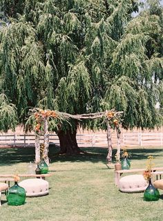 The Weeping Willow tree creates the perfect backdrop for this ceremony site accented with green demijohns in Malibu with Found Vintage Rentals.