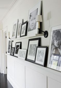 Extra wide trim topping the wainscoting creates space to display a gallery of images. A floating shelf adds another layer of images above. ~ Sarah, Luck Photography.     From Traditional Home Magazine.