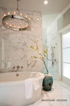 White marble bathroom by Bradshaw Designs circa lighting Roark chandelier over tub