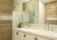 Banheiro branco com detalhe em porcelanato padrão madeira.