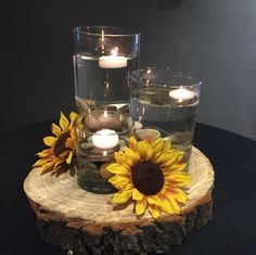 Ann's Room Exclusive. Available in Victoria's Room with (2) vases! Varying cylinder vases filled with neutral stones, water for floating candles on a log round and sunflowers at the base!
