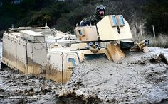 A Royal Marine Viking All Terrain Vehicle negotiates a deep water ditch on Bovington ranges, as part of the joint Royal Marine and Army training package.