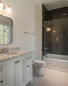 Fantastic bathroom features a white washstand topped with gray marble placed under a Restoration Hardware Astoria Flat Mirror atop a light gray porcelain tiled floor that resembles wood.