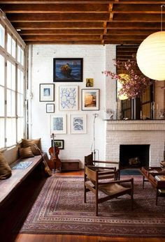 White walls, colorful prints, rich red rug.