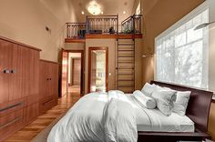 High above the master bedroom sits a lofted home office accessible by ladder.