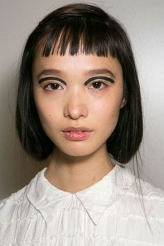 "Karl Lagerfeld asked makeup artist Peter Philips to evoke the look of a ""runaway mormon girl."" To do so, Philips followed each model's eye shape, tracing a graphic black arch just above the crease using Diorshow Waterproof Pro Liner in Carbon. - ELLE.com"