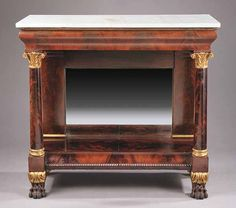 An American Classical Carved and Gilded Mahogany Pier Table, early 19th c., the marble top above an ogee molded frieze, acanthus carved capitals on columns to the front, pilasters framing the mirror plate to the rear, low shelf with gadrooned edge, on acanthus carved paw feet, height 39 3/4 in., width 43 1/4 in., depth 18 3/4 in. [$2500/3500