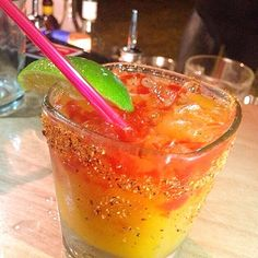 """THE MANGONEADA (pictured) 1 1/2 oz. (45ml) Silver Tequila 1.2 oz. (15ml) Triple Sec 2 oz. (60ml) Mango Puree 1 oz. (30ml) Lime Juice 2 Dashes Tapatio Hot Sauce 2 Dashes Tajin Chili Powder Chamoy Lime Mexican Mango Lollipop Pour all ingredients into a shaker with ice, shake & strain into a margarita glass with chili powder on the rim. The inside of the glass is coated with """"chamoy"""" which is a syrup that's sweet & spicy (candy type) garnish with lime and mexican mango lollipop"""