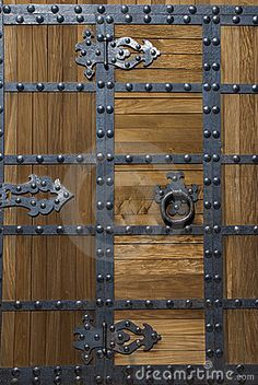 Photo about Close shot of a heavy wooden door with solid metal bolts and handle that protects the entrance to an Asian or Chinese style fortress. Image of slanted, door, protection - 6614892