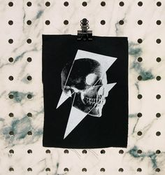 Skull bolt. Based on my original artwork.  Individually hand cut and screen printed by me, out of my studio in Bendigo, Australia. The Details... + Patch is medium-weight black 100% cotton drill + Patch size measures approximately 19cm x 14cm (7.5 x 5.5) + Print size measures approximately 15.5cm x 10.5cm (6.1x 4.1) + Printed with eco-friendly water-based ink + Heat set and machine washable + The edges are un-finished