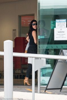 Loosen up: Kim's famous dark tresses were worn loose while North was dressed in a grey onesie for the trip