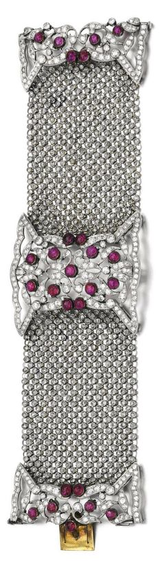 A Belle Epoque ruby and diamond bracelet, early 20th century, composite. Composed of two openwork plaques of pierced scroll work design, millegrain- and collet-set with circular-cut diamonds and cabochon rubies, connected by a fine mesh-link bracelet set with rose diamonds. #BelleÉpoque #bracelet