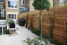 arrière-cour carrelée avec une clôture bois en tant que brise-vue