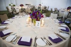 ivory linen, purple napkin and full/low centerpiece. by krystal