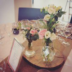 Centre de table composé de trois bouteilles et un rondin de bois. Un vase bouteille de lait, un vase diamant et un vase cou long. Fleurissement champêtre dans les tons de rose et blanc. Réalisation de Lily et Confettis